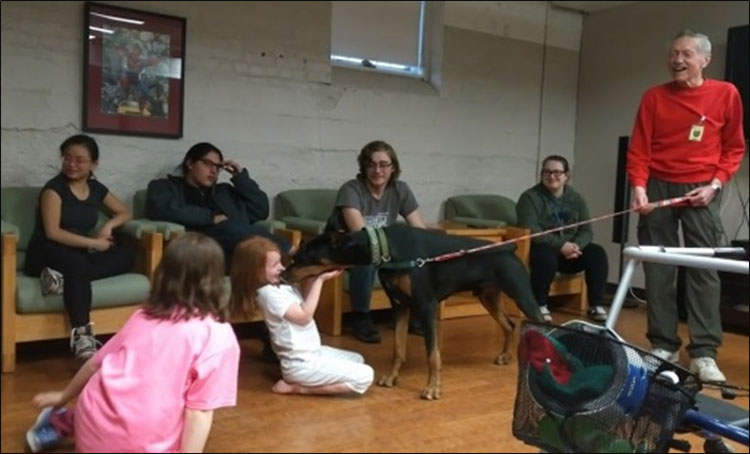 Students spending time with a Deaf Doberman