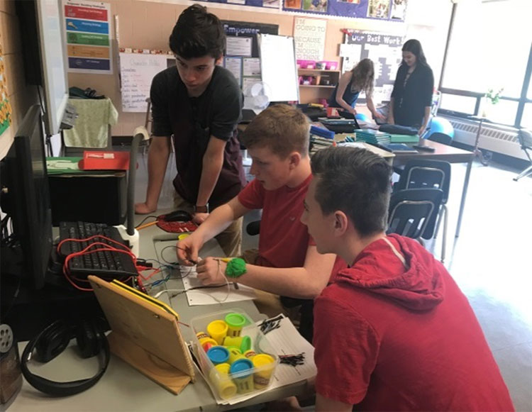 Students using Makey Makey to create video game controllers and a greeter