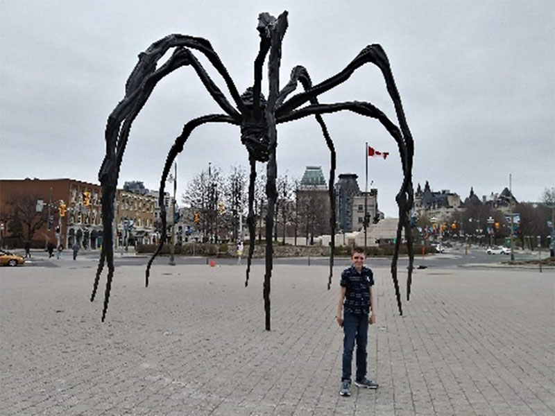 Figure 4: A student posing in front of the Maman statue (a spider sculpture)