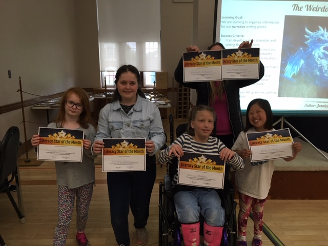 Students holding their literacy stars of the month awards