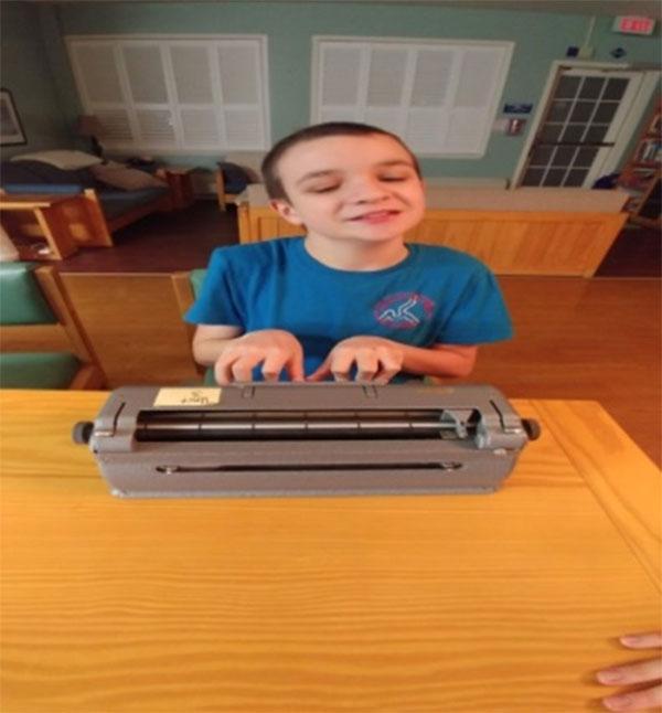 Figure 30 : Élève du primaire qui écrit du braille sur une machine Perkins