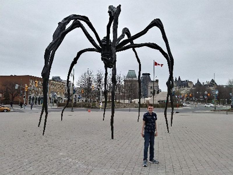 Figure 4 : Un élève posant devant la statue de Maman (sculpture d'araignée)