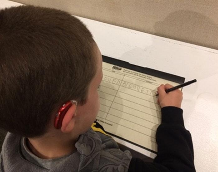 Un élève signe le livre d'invité